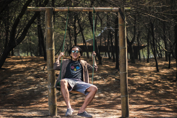 Portrait of young man sitting on swing in forest