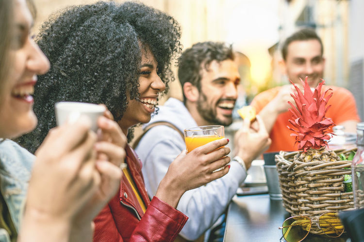People holding drinks and food at table