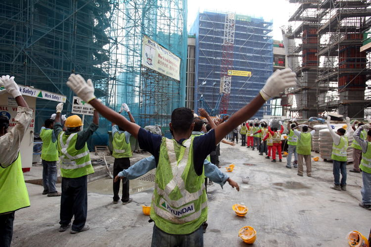 Rear view of workers with arms outstretched standing at construction site