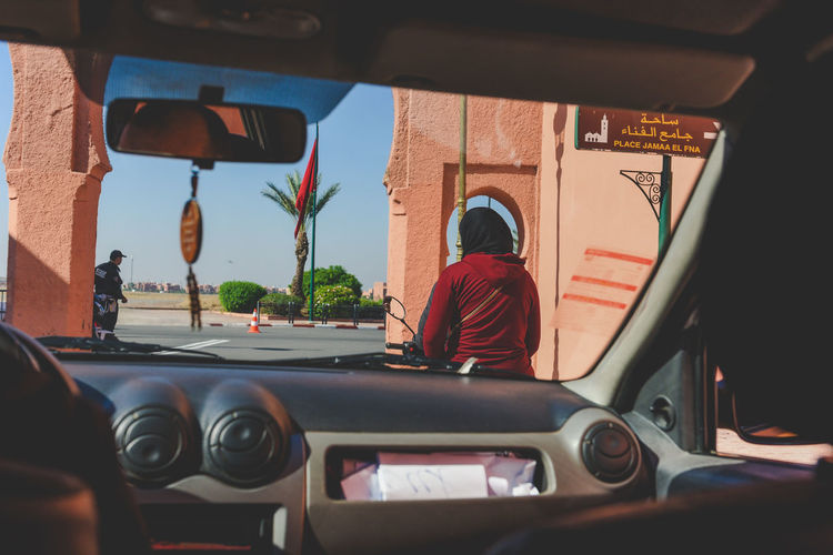 """A woman seen from the front car window driving on a bicycle on a street in Marrakesh. Marrakesh, also known by the French spelling Marrakech, is a major city of the Kingdom of Morocco. It is the fourth largest city in the country, after Casablanca, Fez and Tangier. It is the capital city of the mid-southwestern region of Marrakesh-Safi. Located to the north of the foothills of the snow-capped Atlas Mountains, Marrakesh is situated 580 km (360 mi) southwest of Tangier, 327 km (203 mi) southwest of the Moroccan capital of Rabat, 239 km (149 mi) south of Casablanca, and 246 km (153 mi) northeast of Agadir. The ramparts of Marrakesh, which stretch for some 19 kilometres (12 mi) around the medina of the city, were built by the Almoravids in the 12th century as protective fortifications. The walls are made of a distinct orange-red clay and chalk, giving the city its nickname as the """"red city""""; they stand up to 19 feet (5.8 m) high and have 20 gates and 200 towers along them.[90] Bab Agnaou was built in the 12th century during the Almohad dynasty. The Berber name Agnaou, like Gnaoua, refers to people of Sub-Saharan African origin (cf. Akal-n-iguinawen – land of the black). The gate was called Bab al Kohl (the word kohl also meaning """"black"""") or Bab al Qsar (palace gate) in some historical sources. The corner-pieces are embellished with floral decorations. This ornamentation is framed by three panels marked with an inscription from the Quran in Maghrebi script using foliated Kufic letters, which were also used in Al-Andalus. Bab Agnaou was renovated and its opening reduced in size during the rule of sultan Mohammed ben Abdallah. Bab Aghmat is located east of the Jewish and Muslim cemeteries, and is near the tomb of Ali ibn Yusuf.[91] Bab Berrima with its solid towers stands near the Badi Palace. Bab er Robb (meaning """"Lord's gate"""") is a southern exit from the city, near Bab Agnaou. Built in the 12th century, it provides access to roads leading to the mountain towns of Amizmiz"""