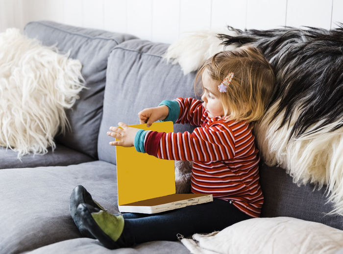 Toddler girl on sofa reading picture book - Hindeloopen, Friesland, Netherlands Baby Babyhood Babygirl Blond Hair Book Caucasian Close-up Comfortable Cozy Confidence  Curiosity Cute Discovery Education Side View Full Length Fur Girl Girls Females Hanging Out Happy Holding Home Individuality Joy Kids Learning Living Room Looking Down Germany People Picture Book Playing Portrait Reading Reading A Book Relaxing Resting Serious Sitting Studying Toddler  Toddlerlife Touching Toy Watching Cushion Hair Clip Hairstyle Furniture Childhood Child Real People Boys One Person Casual Clothing Indoors  Lifestyles Leisure Activity Sofa Males  Home Interior Bed Men Domestic Room Hair Pillow Innocence