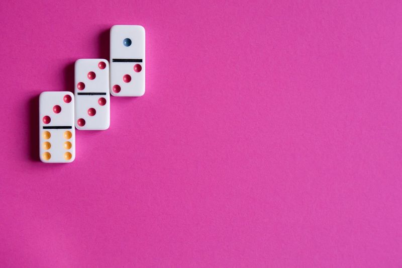 Directly above shot of domino on pink background