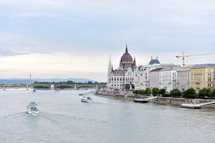 Hungarian Parliament Building By Danube River Against Sky