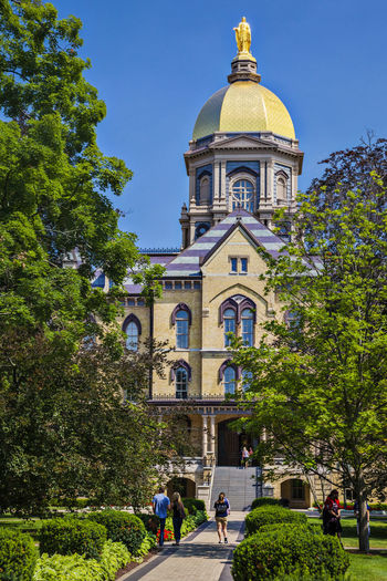 University of Notre Dame USA Green Blue Sky Culture Education Green Grass Religion Science And Technology Tree Campus Christian Color Famous Knowledge Lawn Sculpture Vertical Composition Golden Tower Building Main Building Outdoor Sunny Day University Of Notre Dame USA