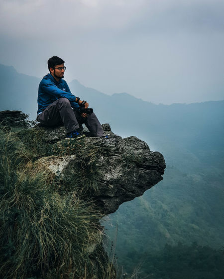 Young man sitting on rock against mountains and sky