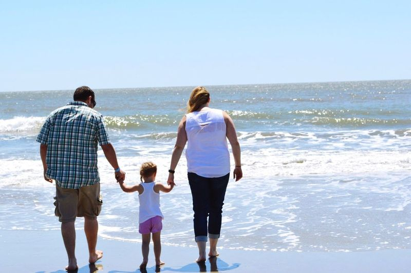 Rear view of parents and daughter walking on beach