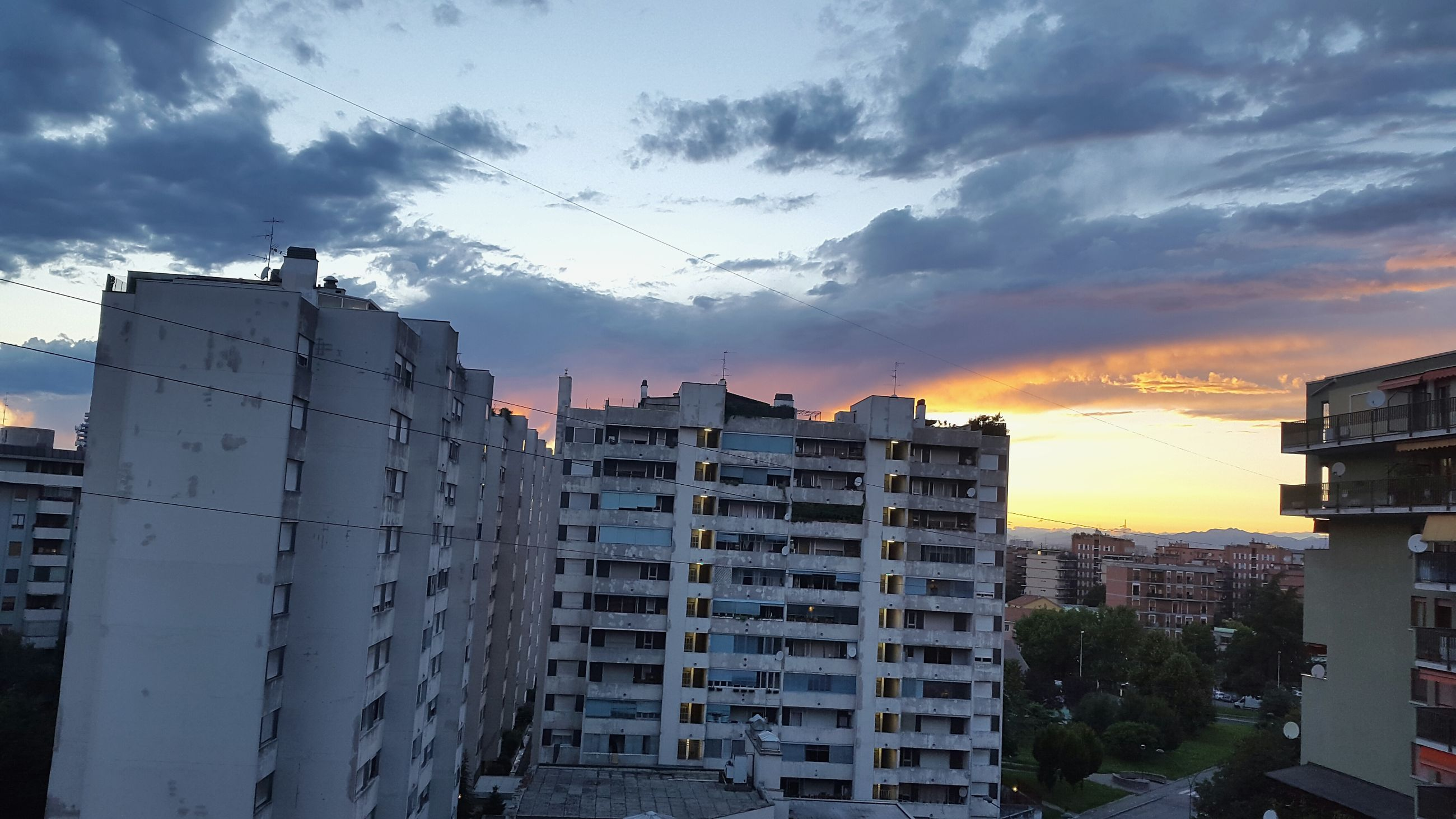 building exterior, architecture, built structure, sky, sunset, cloud - sky, city, cloudy, residential building, residential structure, cloud, building, cityscape, weather, residential district, dusk, overcast, orange color, outdoors, dramatic sky