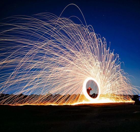 Man spinning illuminated wire wool against sky during dusk