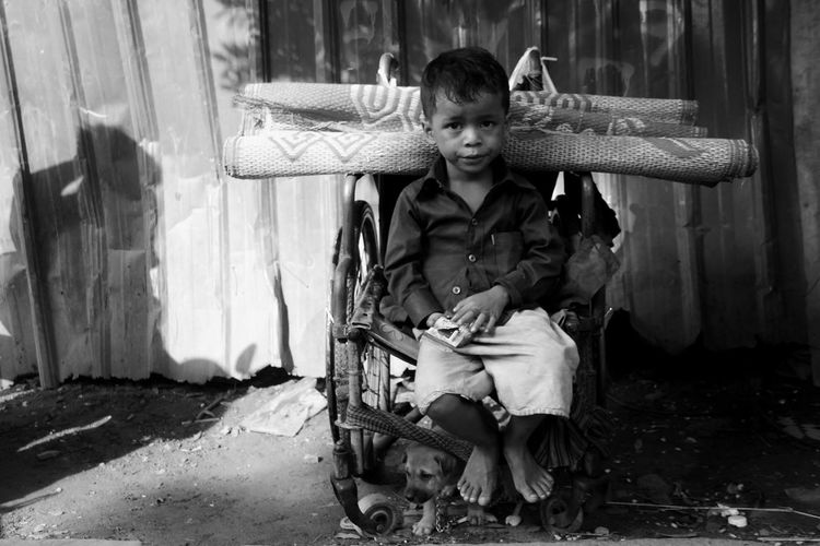 Portrait of boy sitting on old wheelchair with carpet