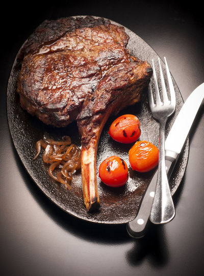 High Angle View Of Roasted Meat Chop And Cherry Tomatoes In Plate