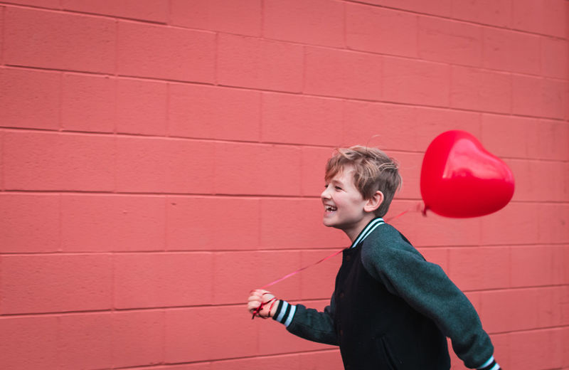 Smiling boy holding balloon while walking by red wall