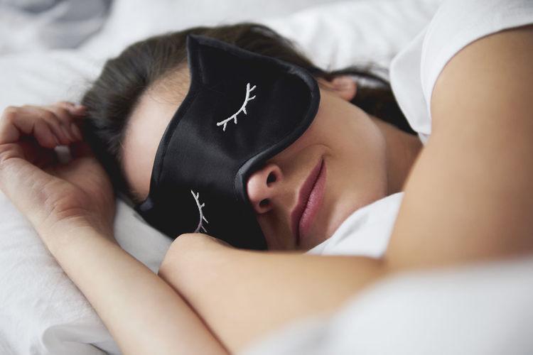 Portrait of woman sleeping on bed