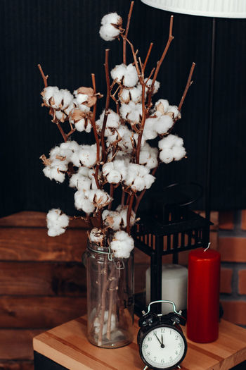 Vase Table Indoors  No People Still Life Flower Flowering Plant Freshness Close-up Fragility Plant Clock Time Nature Vulnerability  Decoration Wood - Material Beauty In Nature Focus On Foreground Lighting Equipment Flower Arrangement Electric Lamp
