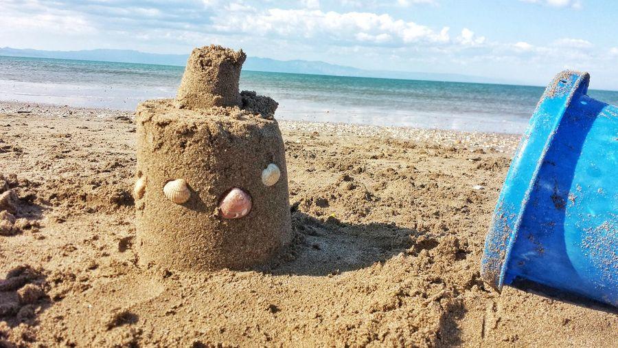 Sandcastle at beach against sky