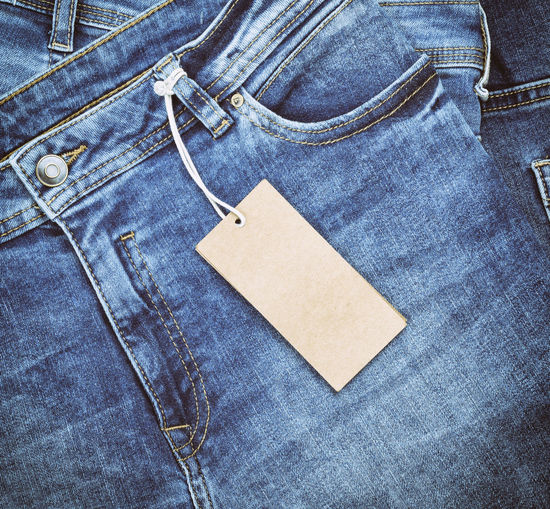 Close-up of labels hanging from jeans