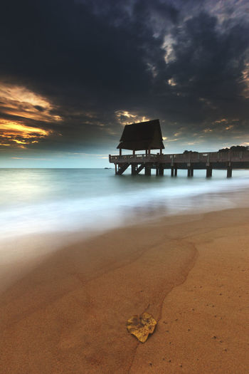 A jetty was build at the beach which is extended to the sea. Capture in portrait format. Beach Beach, Sea, Summer, Sand, Nature, Water, Tropic, Tropical, Wave, Landscape, Background, Ocean, Travel, Shore, Coast, Island, Seascape, Bay, Coastline, Vacation, Splash, Golden, Beautiful, Outdoor, Paradise, Texture, Wavy, Tide, Shoreline, Marine, Lagoon,  Beauty In Nature Day Horizon Over Water Nature No People Outdoors Sand Scenics Sea Shore Silhouette Sky Sunset Tranquil Scene Tranquility Water