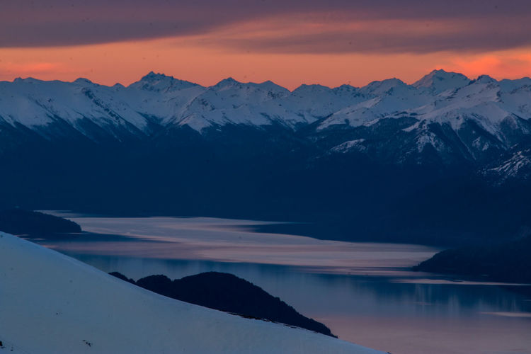 Scenic view of river and snowcapped mountains against sky during sunset