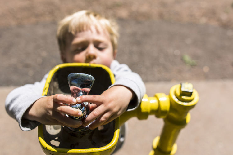 Portrait of boy holding yellow camera