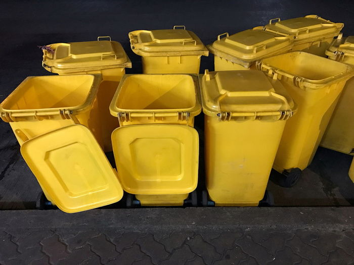 Yellow garbage cans on footpath