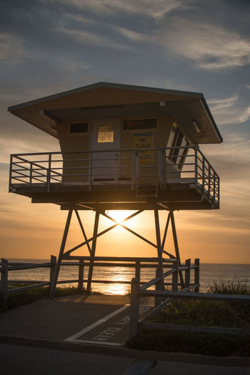 Lifeguard hut at sea shore against sky during sunset