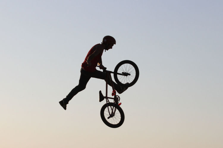 Man with bicycle jumping against clear sky