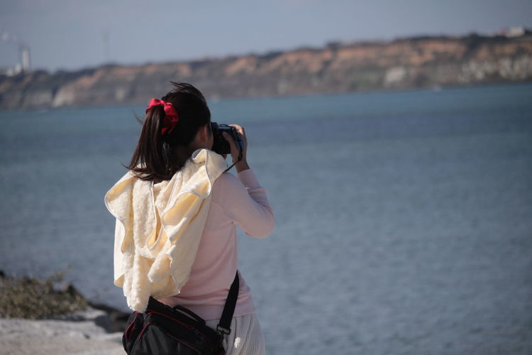 Rear view of woman photographing river