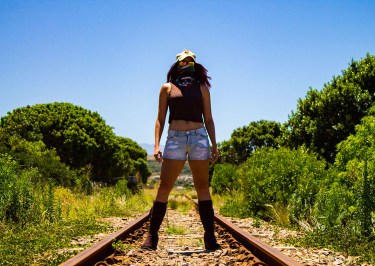 Rear view of man standing on railroad track against sky