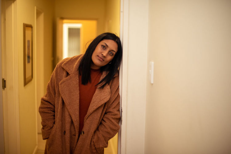 Portrait of woman standing by door at home