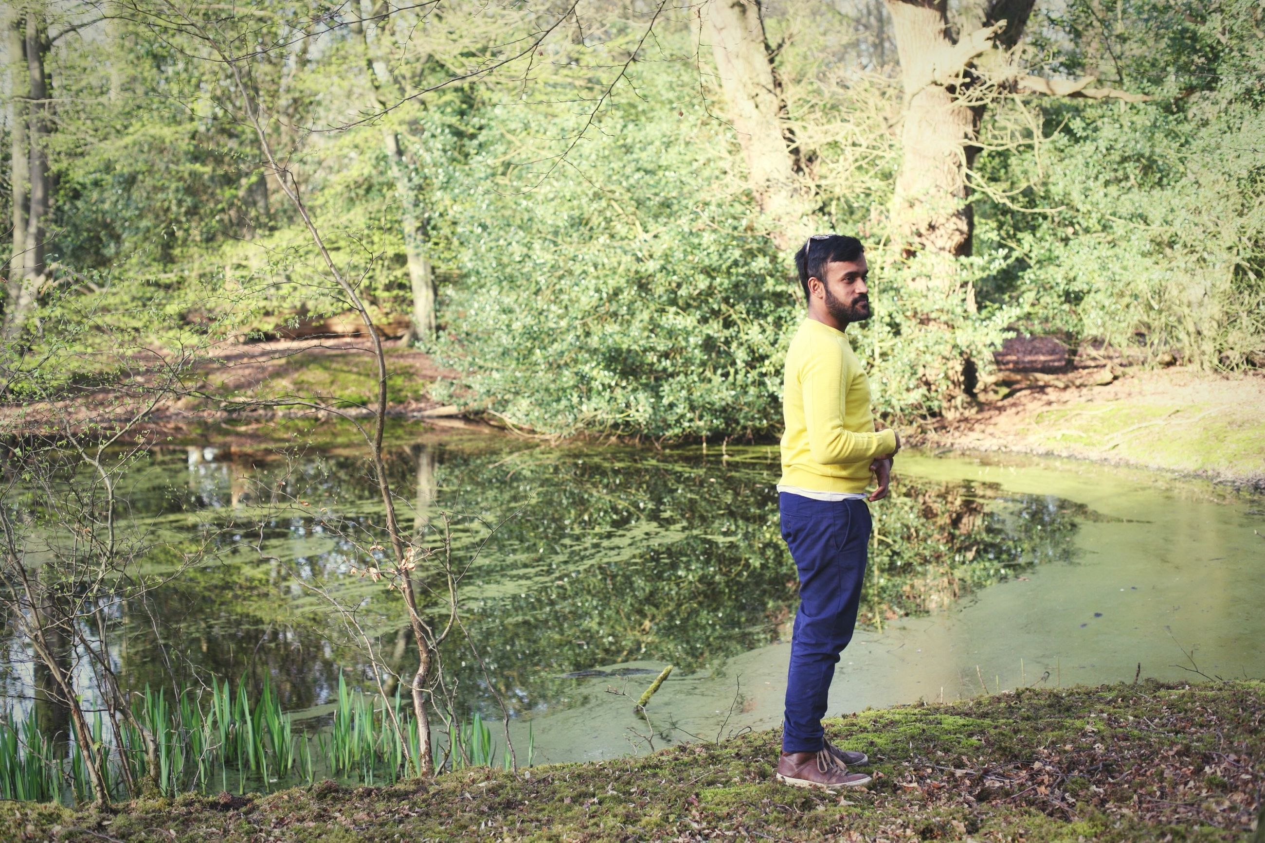 tree, forest, standing, lifestyles, full length, casual clothing, leisure activity, growth, young adult, tree trunk, person, nature, water, plant, tranquility, day, outdoors, three quarter length