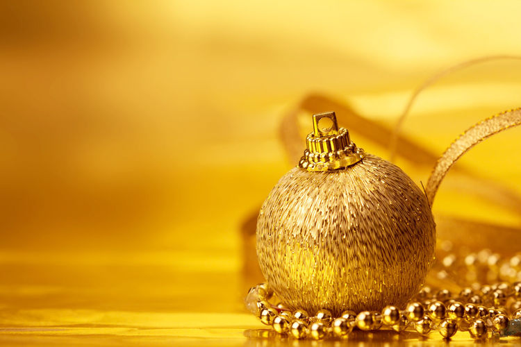 the golden christmas ball decorations for celebration background Bright Celebration Christmas Ornament Close-up Copy Space Decoration Elégance Fashion Gold Gold Colored Indoors  Jewelry Luxury Necklace No People Ornate Pearl Jewelry Personal Accessory Shiny Single Object Sphere Studio Shot Wealth Yellow