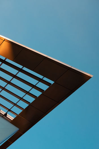 Minimalist photo of the corner of a building against a clear blue sky.