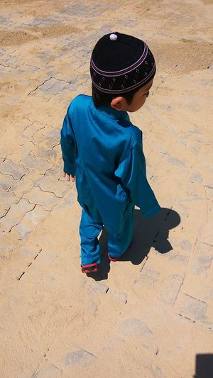 Full Length Of Boy In Traditional Clothing Walking On Footpath During Sunny Day