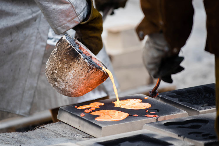 People pouring molten on shape