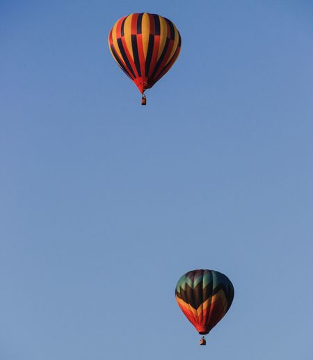 Low angle view of hot air balloons against clear blue sky on sunny day