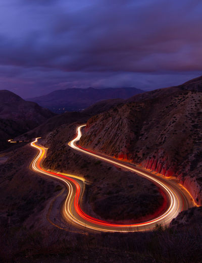 Aerial view of illuminated mountain road against sky at night