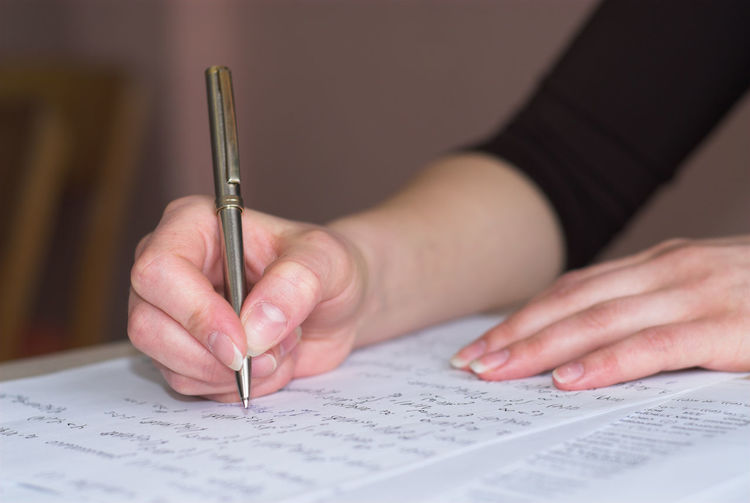 Cropped hand of woman writing on paper
