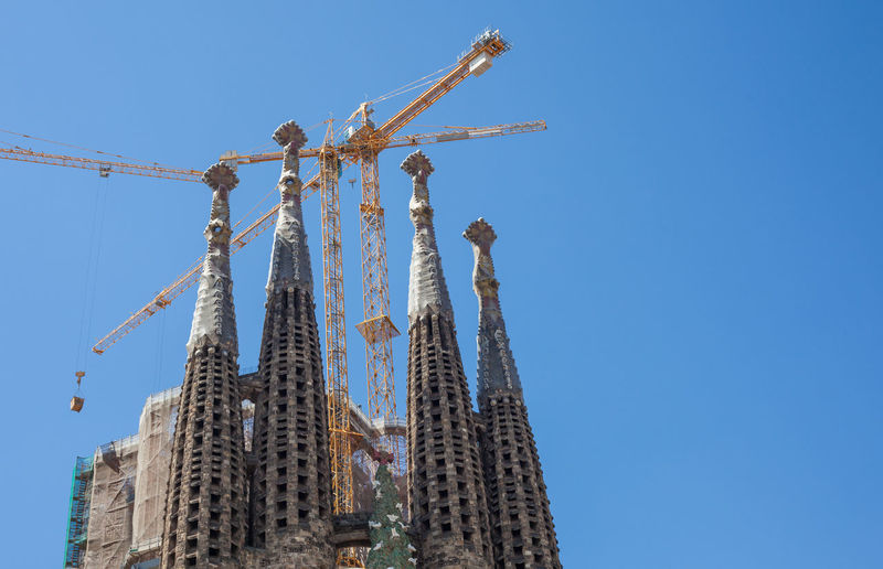 Low angle view of sagrada familia against clear blue sky