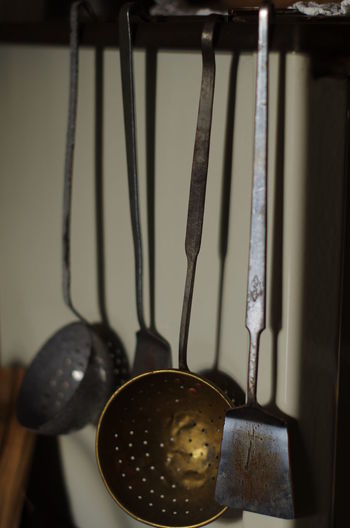 Close-up of ladles and spatulas hanging in kitchen