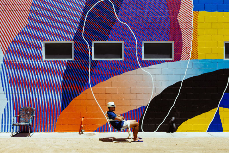 Mural by MOMO at Ace Hotel and Swim Club, Palm Springs, CA. Art Is Everywhere California Chair Hanging Out Momo Palm Springs Palm Springs CA. Adult Art Building Exterior Built Structure Color Burst Colorful Day Design Lifestyles Mural One Person Outdoors Painting Real People Sun