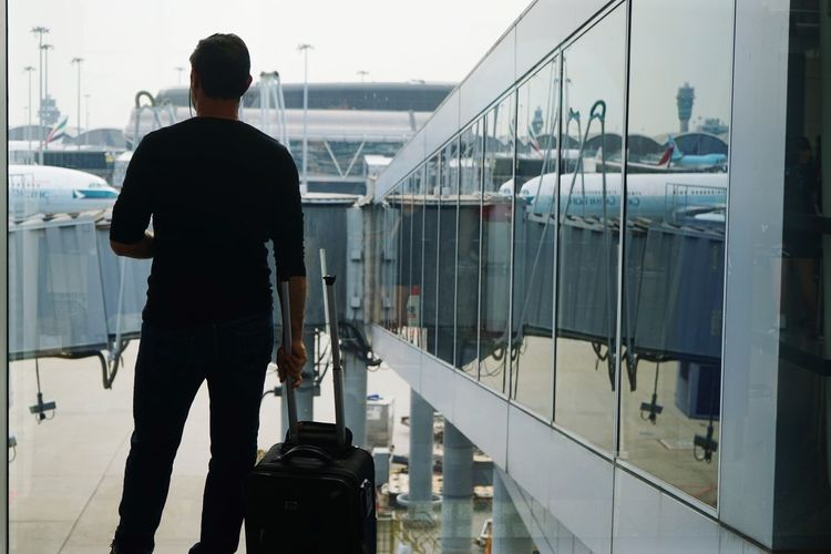 Rear view of man standing on glass window at airport