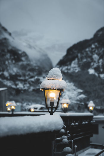 Close-up of illuminated lamp against sky during winter