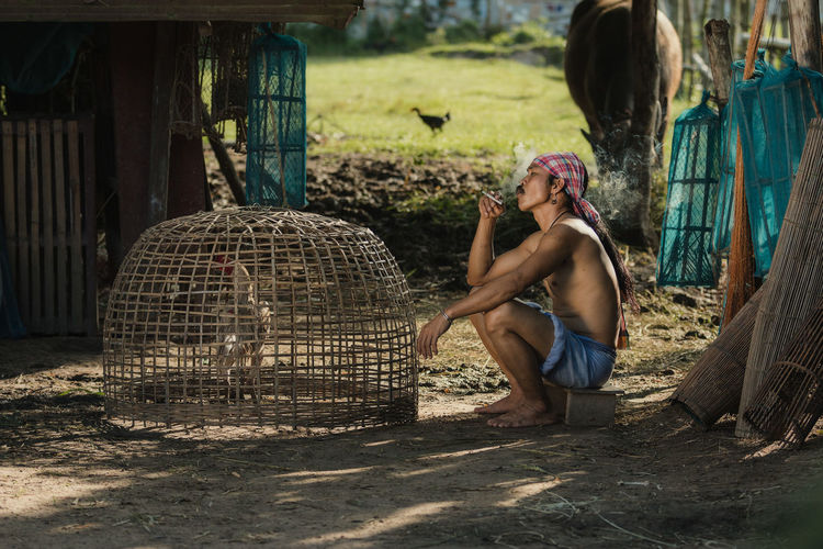 Rural farmer with chicken at countryside,Thailand.The lifestyle of farmer and chickens is a pet in farmland. Adult Animal Wildlife Bird Cage Casual Clothing Day Full Length Leisure Activity Lifestyles Nature One Person Outdoors Real People Sitting Vertebrate Women Young Adult