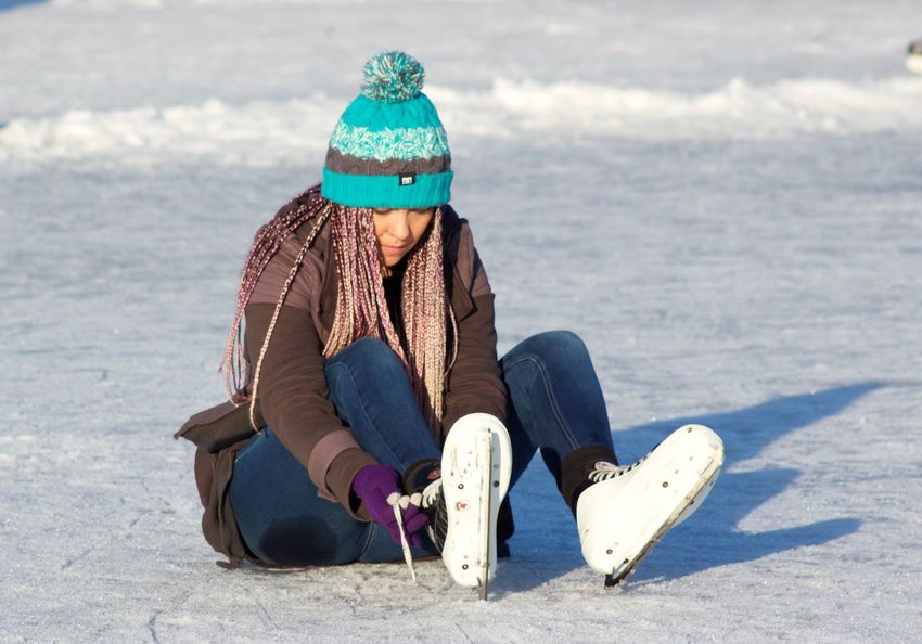 Put that skates on! Ice Skating Leisure Activity Lifestyles Outdoors Sitting Winter Trout Lake Vancouver British Columbia, Canada