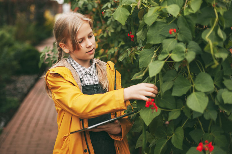 A little girl is exploring nature by writing down her research on a tablet. curious children