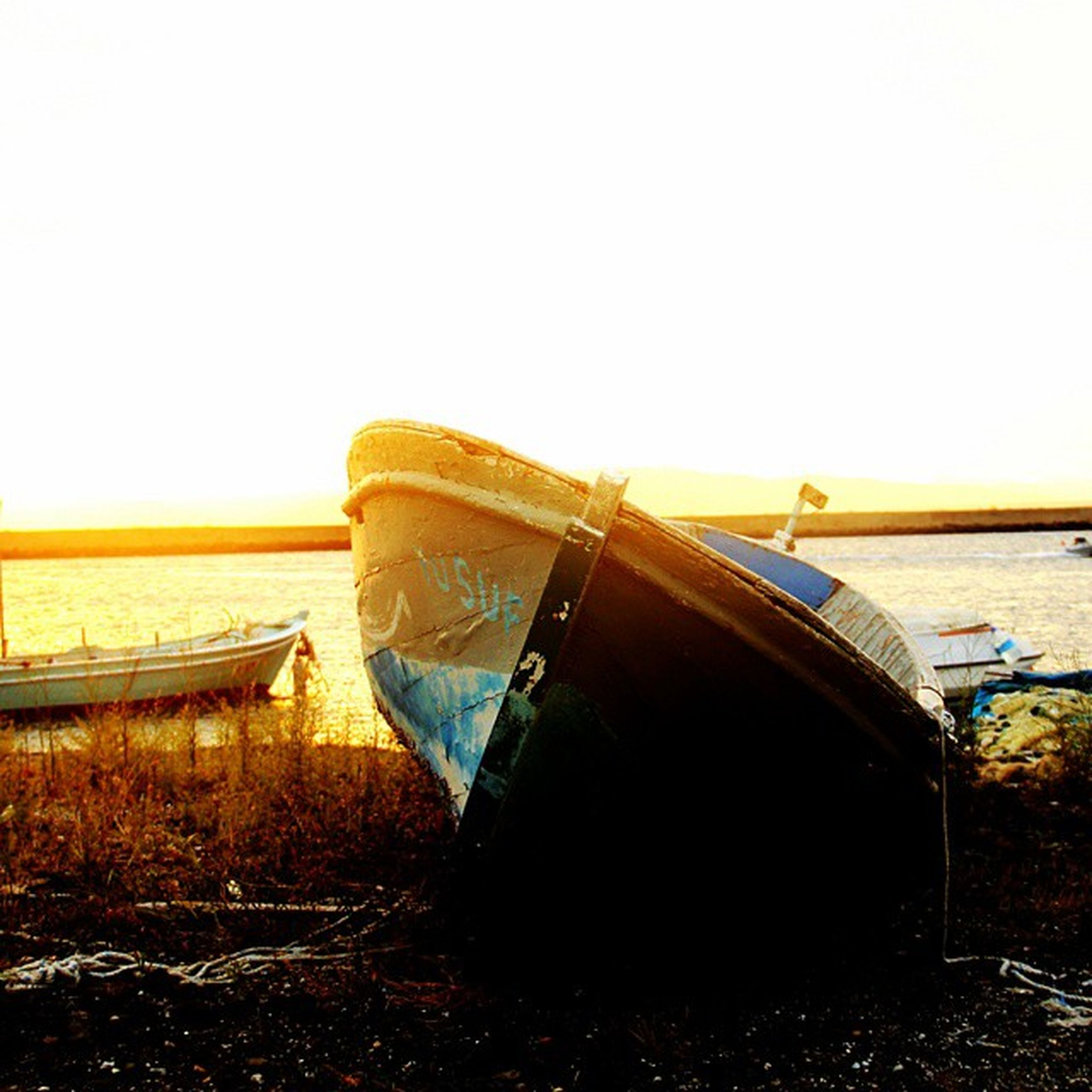 transportation, clear sky, mode of transport, nautical vessel, boat, copy space, water, moored, sea, abandoned, outdoors, travel, no people, sky, nature, tranquility, beach, sunlight, land vehicle, tranquil scene
