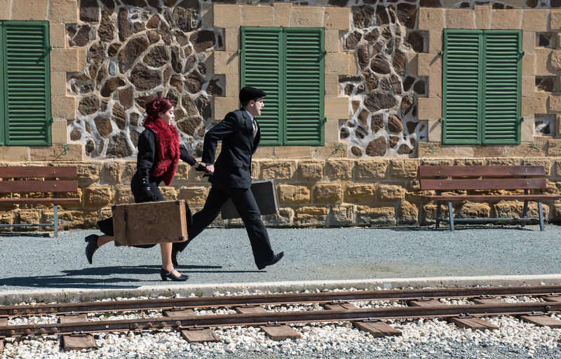 Full Length Of People With Suitcase Walking On Railroad Station Platform