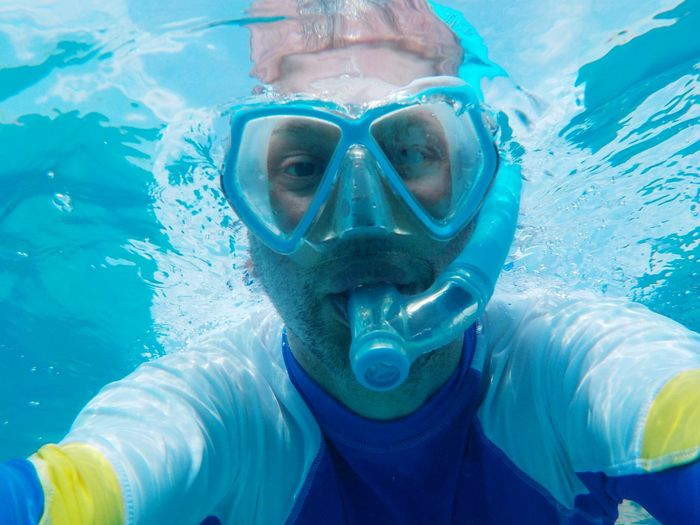 Close-up low angle portrait of man snorkeling undersea