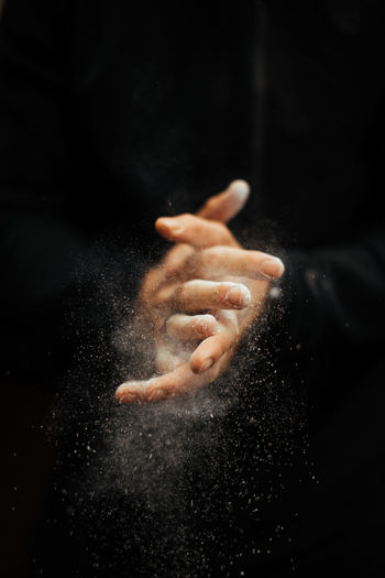 Cropped Hands Of Man Dusting Sports Chalk Against Black Background