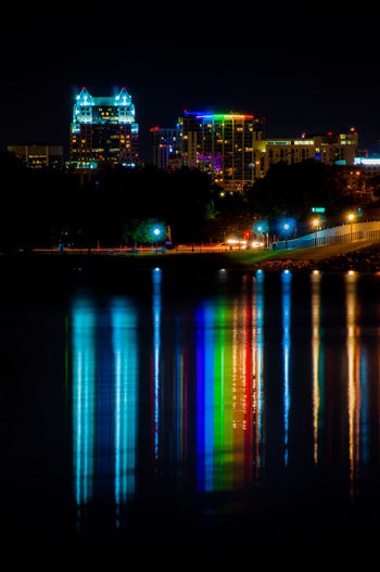 Illuminated buildings by river at night