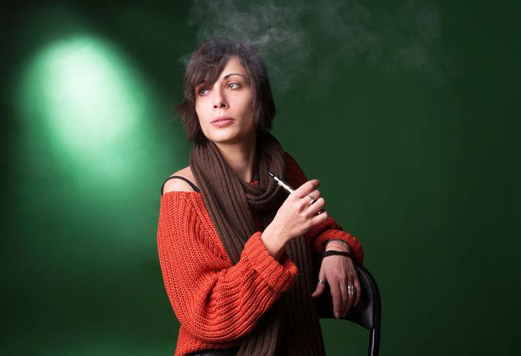 Young Woman Using Electric Cigarette While Sitting Against Green Background